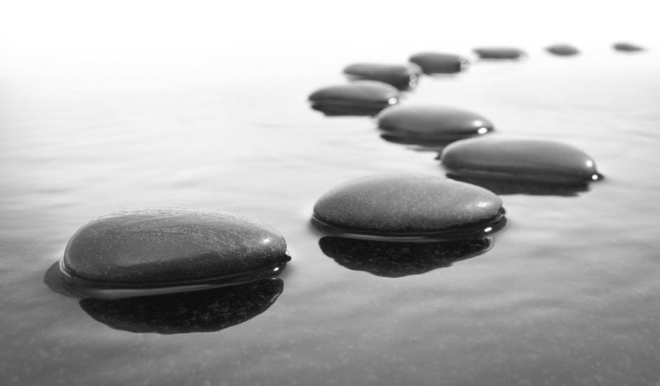 black pebbles in water arranged in s-shape